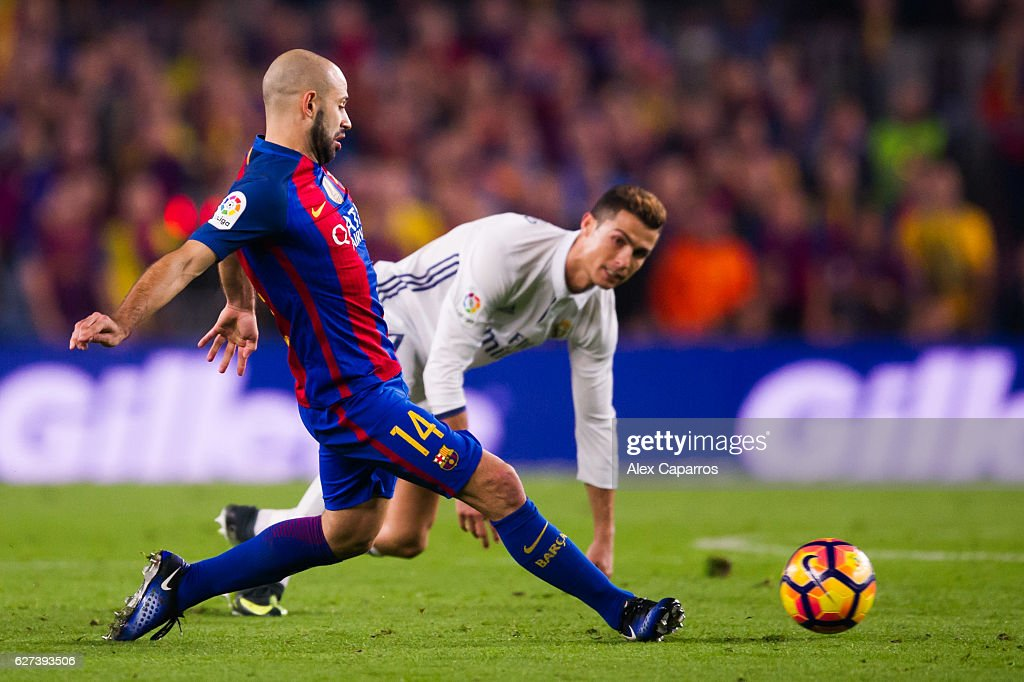 Javier Mascherano of FC Barcelona plays the ball past Cristiano Ronaldo of Real Madrid CF during the La Liga match between FC Barcelona and Real...