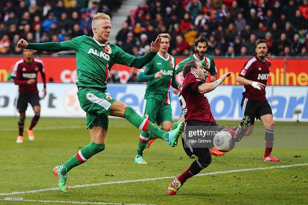Javier Pinola of Nuernberg blocks a shot by Kevin Voigt of Augsburg during the Bundesliga match between FC Augsburg and 1 FC Nuernberg at SGL Arena...