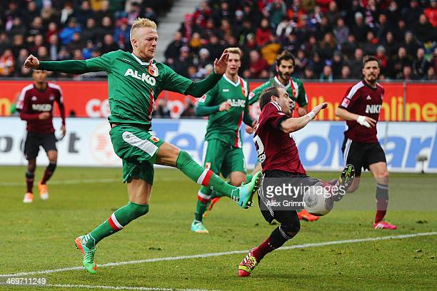 Javier Pinola of Nuernberg blocks a shot by Kevin Voigt of Augsburg during the Bundesliga match between FC Augsburg and 1 FC Nuernberg at SGL Arena...