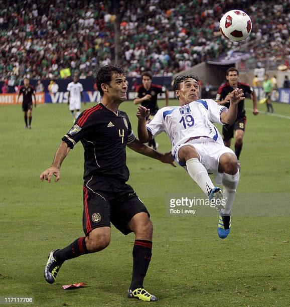 Javier Portillo of Honduras clears the ball away from Rafael Marquez of Mexico in the first half at Reliant Stadium on June 22 2011 in Houston Texas