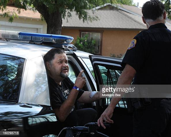 Javier Salcedo argues with a police officer right as he is put into a police vehicle in front of his residence in Modesto California on Tuesday...