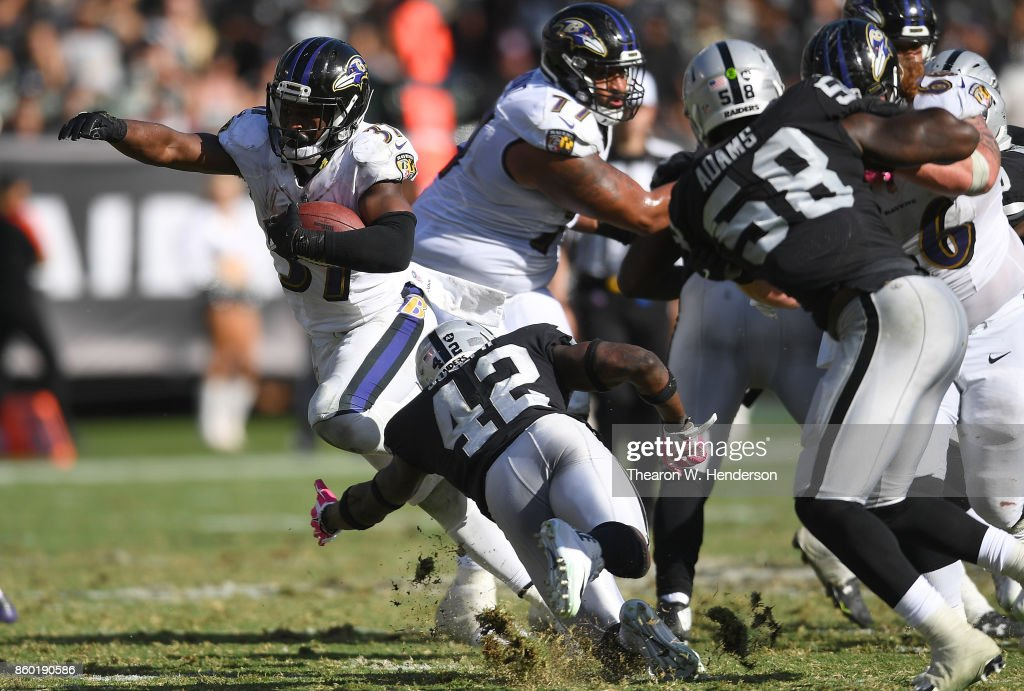 Javorius Allen #37 of the Baltimore Ravens carries runs through the tackle of Karl Joseph #42 of the Oakland Raiders during the fourth quarter of their NFL football game at Oakland-Alameda County Coliseum on October 8, 2017 in Oakland, California.