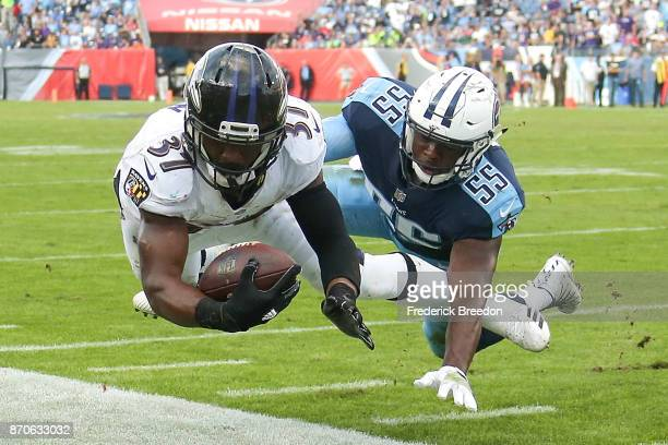 Javorius Allen of the Baltimore Ravens dives towards the endzone pylon but comes up short as he is tackled by Jayon Brown of the Tennessee Titans...