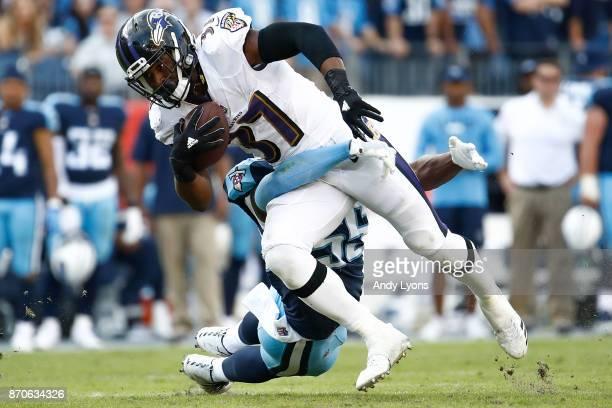Javorius Allen of the Baltimore Ravens runs up the field tackled by Jayon Brown of the Tennessee Titans during the second half at Nissan Stadium on...