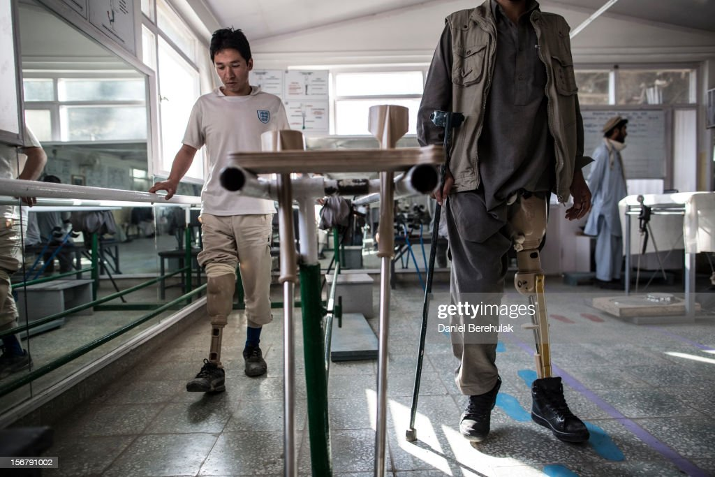 M. Jawad, 21, (L) an Afghan National Police (ANP) officer who lost his leg after stepping on an IED while on patrol a year ago, practices walking on his prosthetic leg at the International Committee of the Red Cross (ICRC), orthopedic centre on November 20, 2012 in Kabul, Afghanistan. The ICRC rehabilitation centre works to educate and rehabilitate land-mine victims, and those with limb related deformities, back into society and employment offering micro-credit financing, home schooling and vocational training to patients. The clinic itself is unique in that all of the workers are handicapped. The ICRC centre in Kabul has registered over 57,000 patients and 114,000 countrywide in all of their centres since its inception 25 years ago.