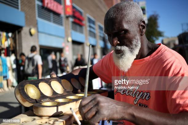 Jawarah a citizen of Antigua works on Wari game popular in the Caribbean and West Africa on 125th street of Harlem neighborhood of New York City...