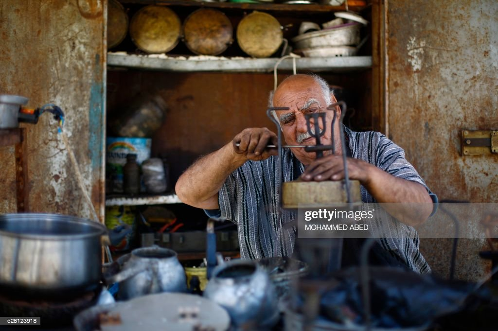 Jawdat Al-Khor, a 73-year-old Palestinian man, fixes an old stove in his shop in Gaza City on May 4, 2016. / AFP / MOHAMMED