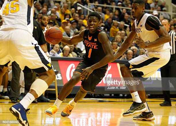 Jawun Evans of the Oklahoma State Cowboys drives to the basket during the game against Jonathan Holton of the West Virginia Mountaineers at the WVU...