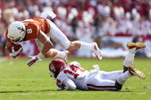 Jaxon Shipley of the Texas Longhorns carries the ball against Aaron Colvin of the Oklahoma Sooners in the second quarter at the Cotton Bowl on...