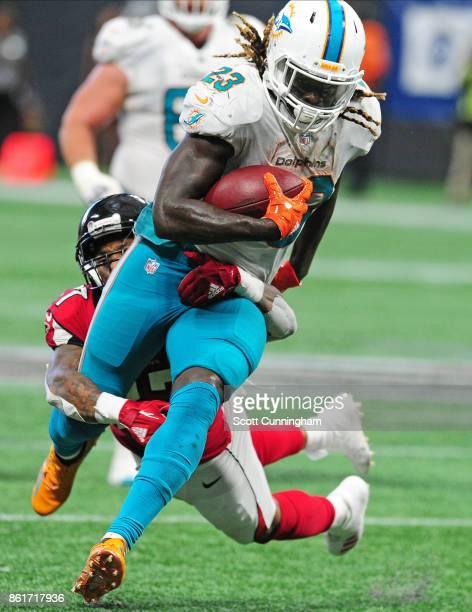 Jay Ajayi of the Miami Dolphins carries the ball against Ricardo Allen of the Atlanta Falcons at MercedesBenz Stadium on October 15 2017 in Atlanta...