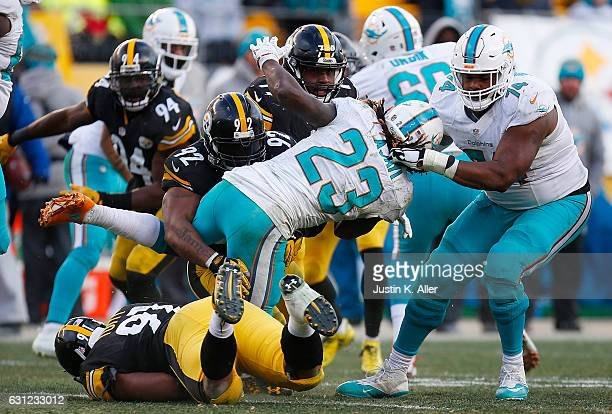 Jay Ajayi of the Miami Dolphins is wrapped up for a tackle by James Harrison of the Pittsburgh Steelers in the second half during the AFC Wild Card...