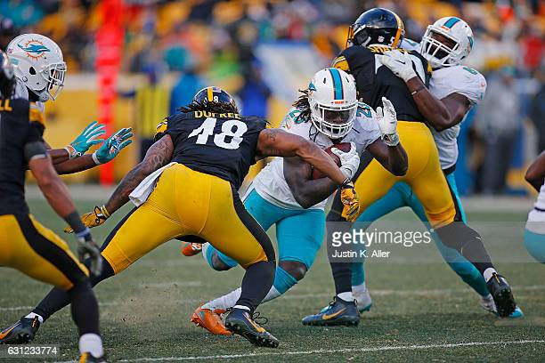 Jay Ajayi of the Miami Dolphins rushes against Bud Dupree of the Pittsburgh Steelers in the second half during the AFC Wild Card Playoff game at...