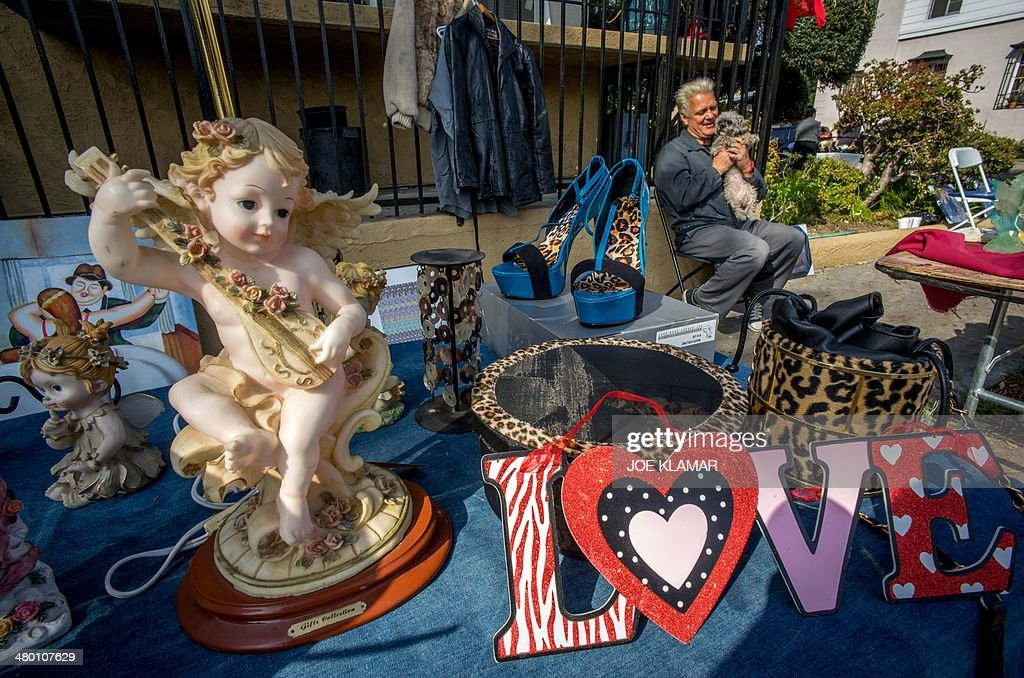 Jay and his pooch Sissy waits for potential offering a nice variety of angels and other items at her garage sale in mid-city of Los Angeles on March 22, 2014.