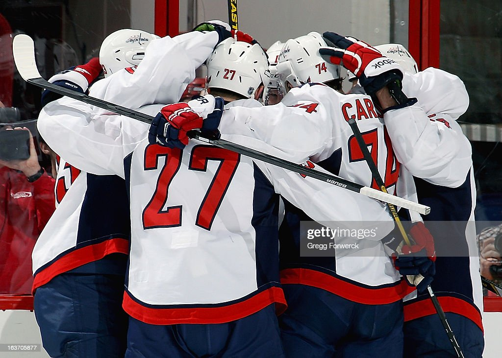 Jay Beagle #83, Karl Azner #27, John Carlson #74 and Aaron Volpatti #24 of the Washington Capitals celebrate a second-period goal scored by Joey Crabb #15 against the Carolina Hurricanes during their NHL game at PNC Arena on March 14, 2013 in Raleigh, North Carolina.