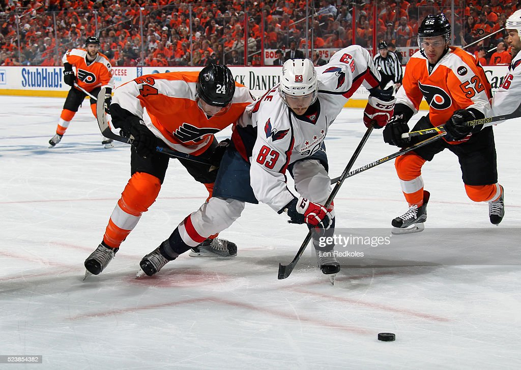 Jay Beagle of the Washington Capitals battles for control of the puck following a faceoff against Matt Read and Nick Cousins of the Philadelphia...