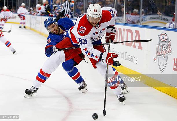 Jay Beagle of the Washington Capitals battles for the puck against Dominic Moore of the New York Rangers in Game One of the Eastern Conference...