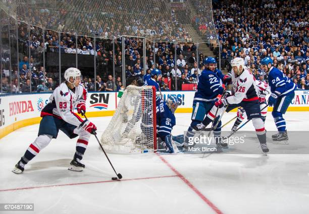 Jay Beagle of the Washington Capitals brings the puck around with teammate Daniel Winnik against Frederik Andersen and Nikita Zaitsev of the Toronto...