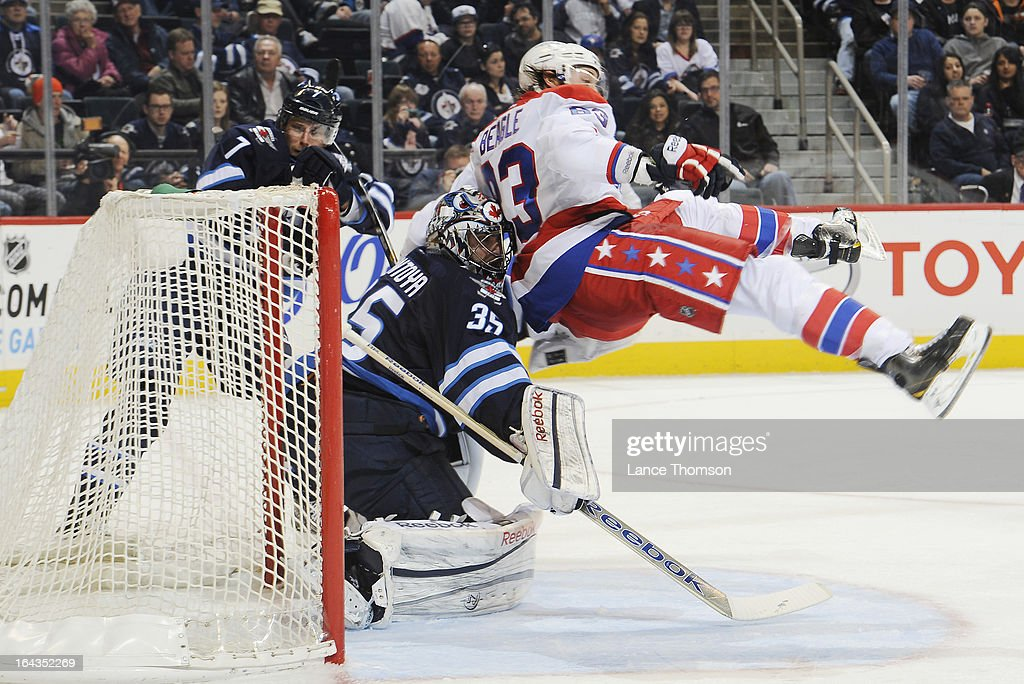 Jay Beagle #83 of the Washington Capitals goes airborne as he crashes into goaltender Al Montoya #35 of the Winnipeg Jets during third period action at the MTS Centre on March 22, 2013 in Winnipeg, Manitoba, Canada.