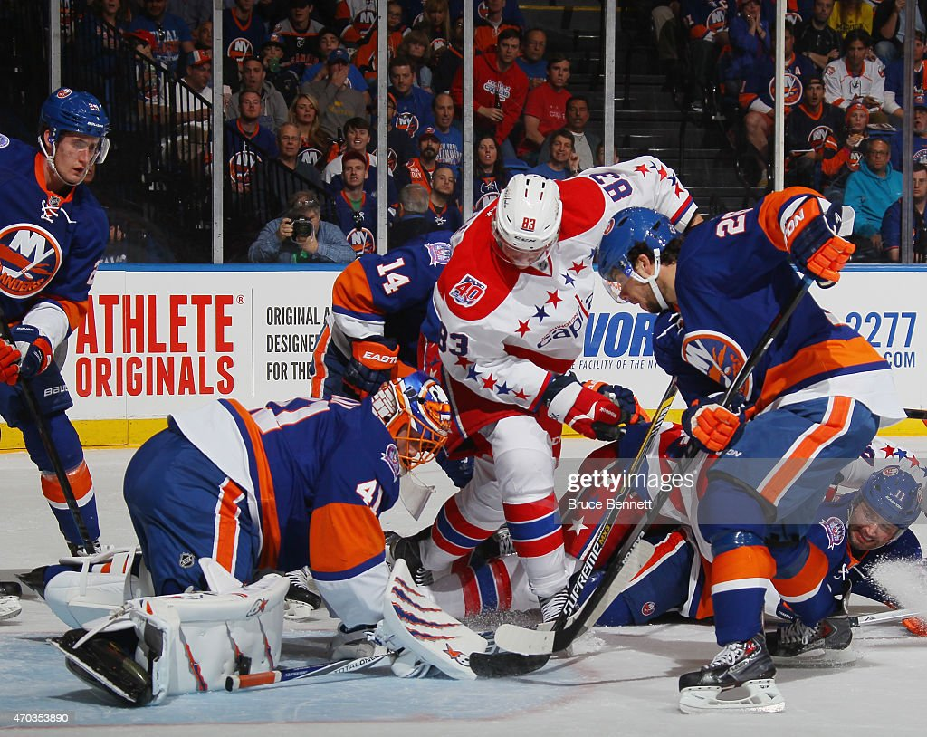 Jay Beagle of the Washington Capitals looks for the rebound as the puck bounces off the leg pad of Jaroslav Halak of the New York Islanders during...