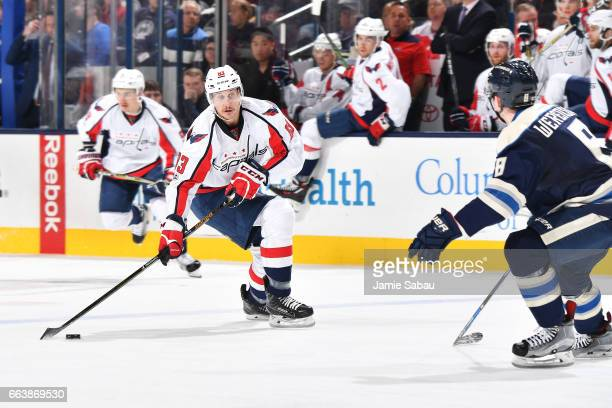 Jay Beagle of the Washington Capitals skates the puck towards Zach Werenski of the Columbus Blue Jackets during the second period of a game on April...