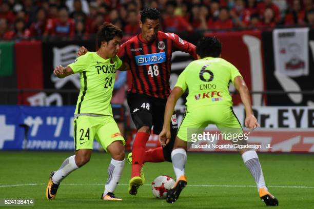 Jay Bothroyd of Consadole Sapporo competes for the ball against Takahiro Sekine and Wataru Endo of Urawa Red Diamonds during the JLeague J1 match...