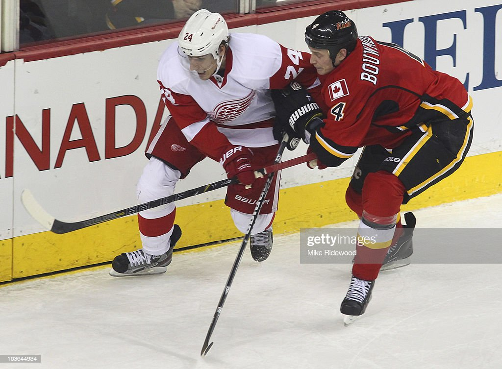 <a gi-track='captionPersonalityLinkClicked' href=/galleries/search?phrase=Jay+Bouwmeester&family=editorial&specificpeople=201875 ng-click='$event.stopPropagation()'>Jay Bouwmeester</a> #4 of the Calgary Flames checks <a gi-track='captionPersonalityLinkClicked' href=/galleries/search?phrase=Damien+Brunner&family=editorial&specificpeople=6931570 ng-click='$event.stopPropagation()'>Damien Brunner</a> #24 of the Detroit Red Wings during third period NHL action on March 13, 2013 at the Scotiabank Saddledome in Calgary, Alberta, Canada. Calgary Flames defeated the Detroit Red Wings 5 - 2.