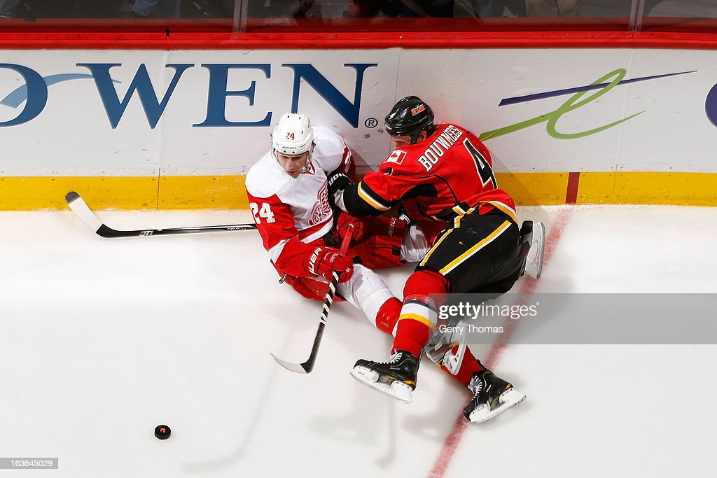 <a gi-track='captionPersonalityLinkClicked' href=/galleries/search?phrase=Jay+Bouwmeester&family=editorial&specificpeople=201875 ng-click='$event.stopPropagation()'>Jay Bouwmeester</a> #4 of the Calgary Flames falls to the ice with <a gi-track='captionPersonalityLinkClicked' href=/galleries/search?phrase=Damien+Brunner&family=editorial&specificpeople=6931570 ng-click='$event.stopPropagation()'>Damien Brunner</a> #24 of the Detroit Red Wings on March 13, 2013 at the Scotiabank Saddledome in Calgary, Alberta, Canada.