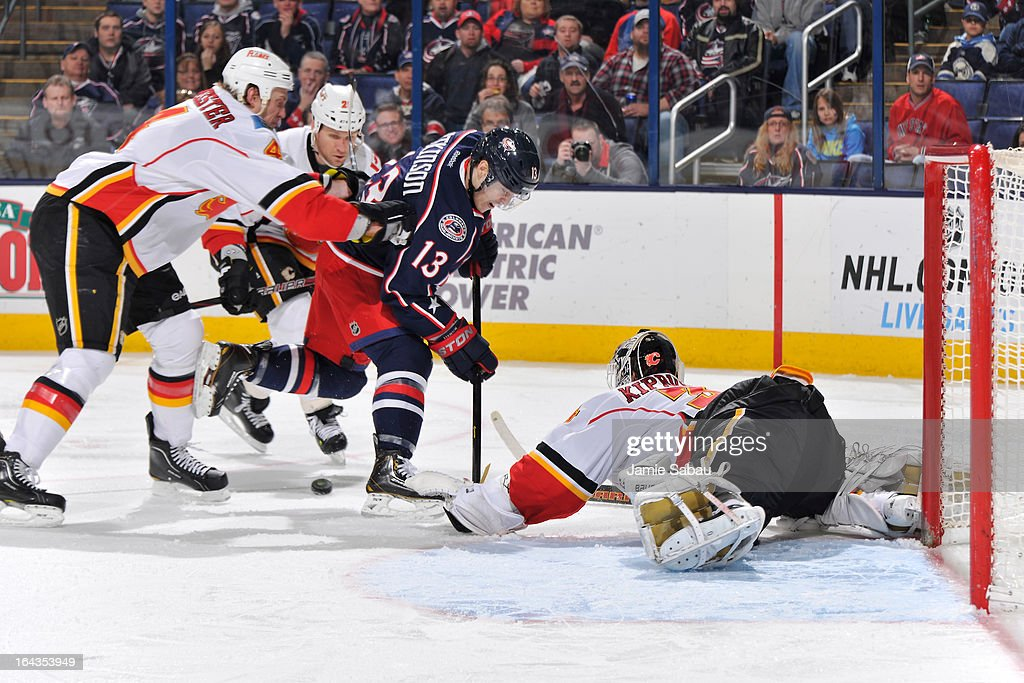 Jay Bouwmeester #4 of the Calgary Flames pushes Cam Atkinson #13 of the Columbus Blue Jackets off the puck during the third period on March 22, 2013 at Nationwide Arena in Columbus, Ohio. Columbus defeated Calgary 5-1.