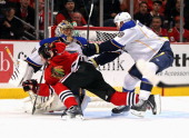 Jay Bouwmeester of the St Louis Blues shoves Andrew Shaw of the Chicago Blackhawks to the ice in front of Jaroslav Halak at the United Center on...