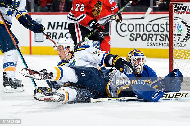 Jay Bouwmeester of the St Louis Blues slides into goalie Brian Elliott in the first period of the NHL game against the Chicago Blackhawks at the...