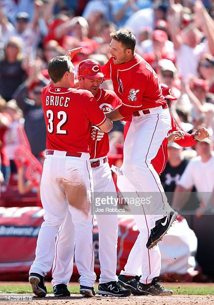 Jay Bruce and Chris Heisey of the Cincinnati Reds celebrate with teammate Scott Rolen after his gamewinning hit in the bottom of the ninth inning...