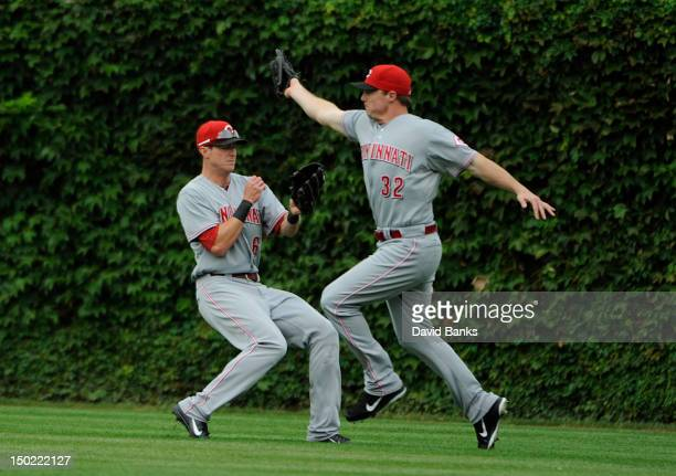 Jay Bruce of the Cincinnati Reds makes a catch in front of Drew Stubbs against the Chicago Cubs in the fourth inning on August 12 2012 at Wrigley...