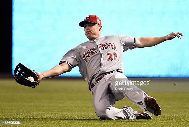 Jay Bruce of the Cincinnati Reds makes a sliding catch on a ball hit by Clint Barmes of the San Diego Padres during the seventh inning of a baseball...