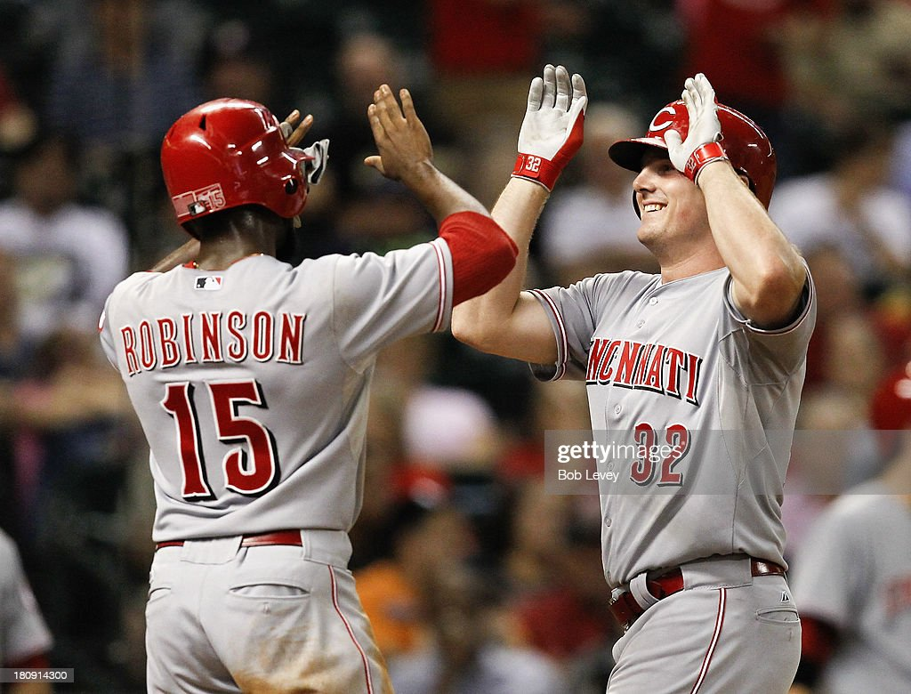 Jay Bruce #32 of the Cincinnati Reds receives high fives from Derrick Robinson #15 of the Cincinnati Reds after hitting a grand slam to left field in the fourth inning against the Houston Astros at Minute Maid Park on September 17, 2013 in Houston, Texas.