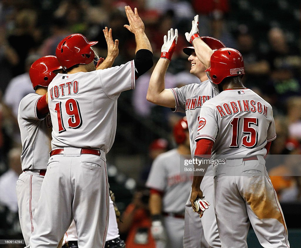 Jay Bruce #32 of the Cincinnati Reds receives high fives from Joey Votto #19 of the Cincinnati Reds of the Cincinnati Reds along with Derrick Robinson #15 and Shin-Soo Choo #17 of the Cincinnati Reds after hitting a grand slam to left field in the fourth inning against the Houston Astros at Minute Maid Park on September 17, 2013 in Houston, Texas.