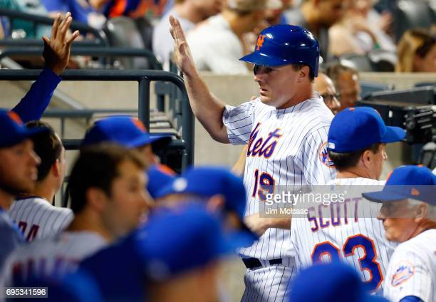 Jay Bruce of the New York Mets celebrates with his teammates in the dugout after scoring a run in the eighth inning against the Chicago Cubs at Citi...