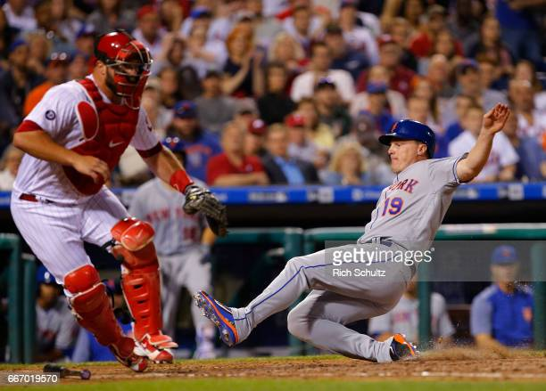 Jay Bruce of the New York Mets slides safely into home plate before catcher Cameron Rupp of the Philadelphia Phillies gets the ball on a sacrifice...