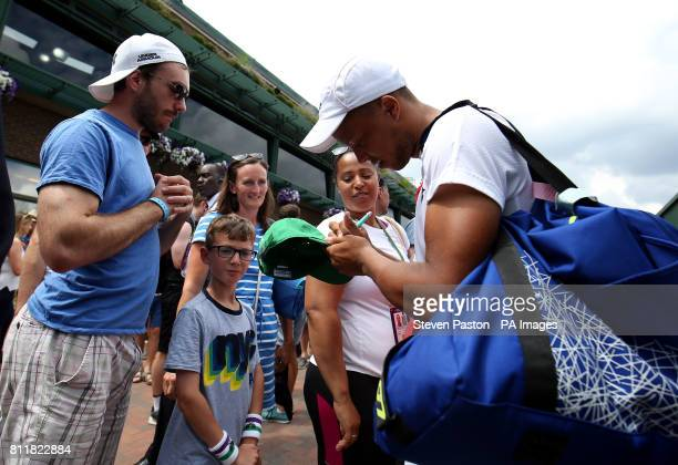 Jay Clarke signs autographs for fans after his doubles match with Marcus Willis on day seven of the Wimbledon Championships at The All England Lawn...
