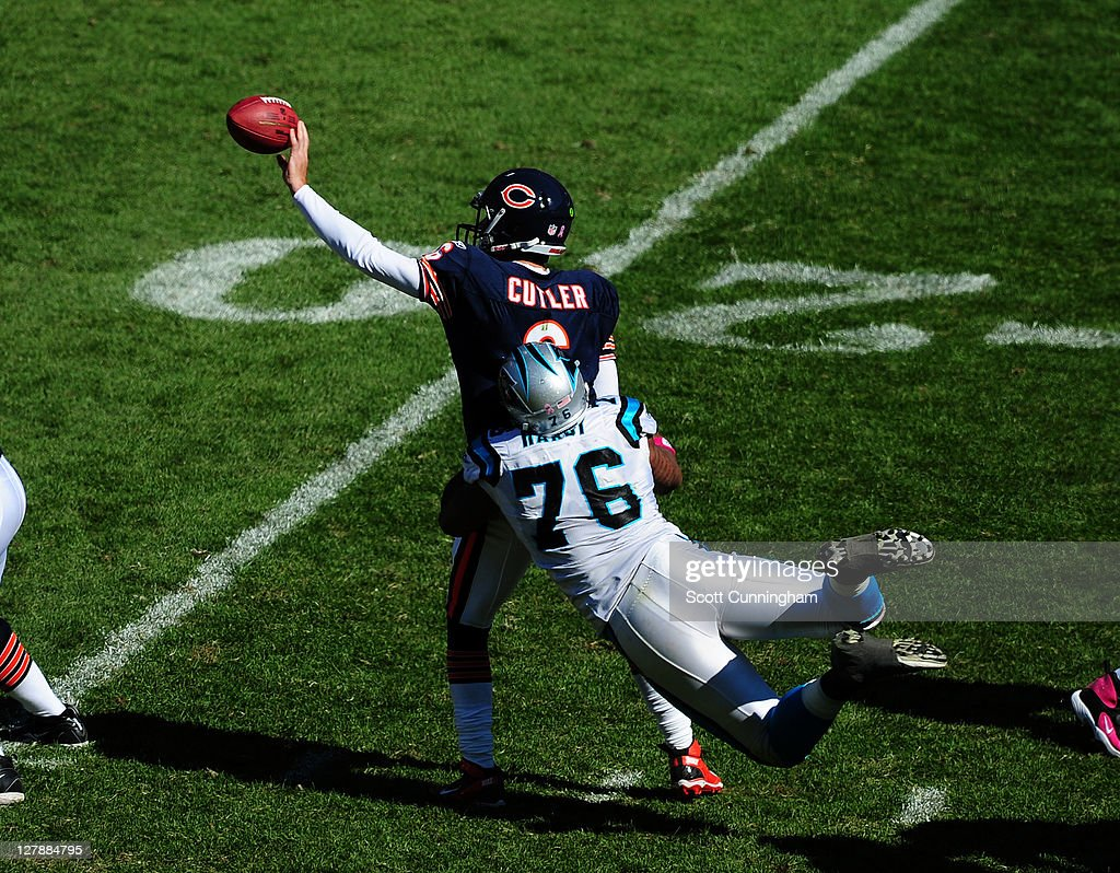 Jay Cutler #6 of the Chicago Bears flips a pass against Greg Hardy #76 of the Carolina Panthers at Soldier Field on October 2, 2011 in Chicago, Illinois.