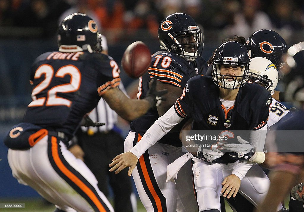 Jay Cutler of the Chicago Bears flips the ball to Matt Forte as he is hit by Antwan Barnes of the San Diego Chargers at Soldier Field on November 20...