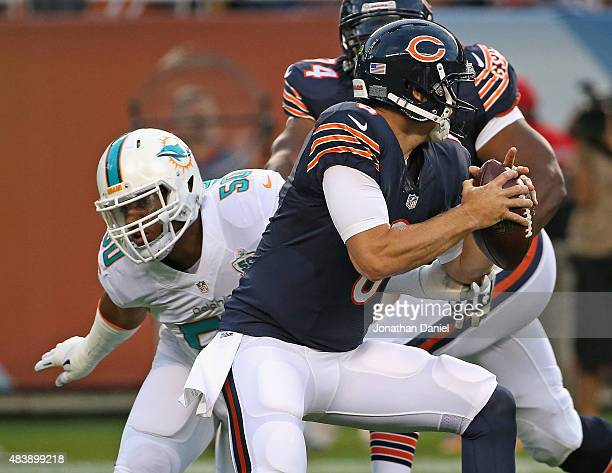Jay Cutler of the Chicago Bears gets away from Olivier Vernon of the Miami Dolphins during a preseason game at Soldier Field on August 13 2015 in...
