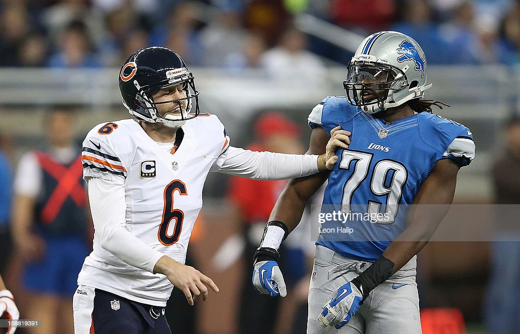 Jay Cutler #6 of the Chicago Bears gives Willie Young #79 of the Detroit Lions a push during the game at Ford Field on December 30, 2012 in Detroit, Michigan. The Bears defeted the Lions 26-24.