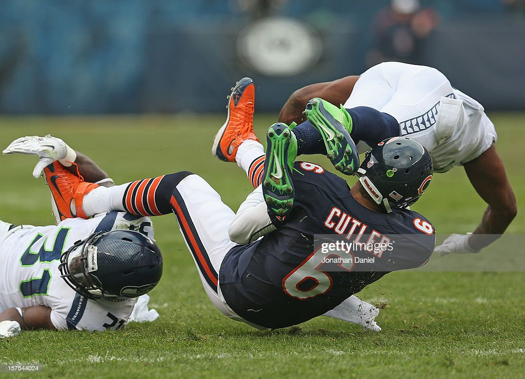Jay Cutler #6 of the Chicago Bears is brought down by Kam Chancellor #31 and Earl Thomas #29 of the Seattle Seahawks at Soldier Field on December 2, 2012 in Chicago, Illinois. The Seahawks defeated the Bears 23-17 in overtime.