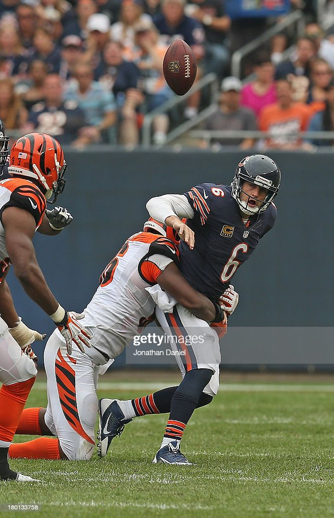 Jay Cutler #6 of the Chicago Bears is hit after passing by Carolos Dunlap #96 of the Cincinnati Bengals at Soldier Field on September 8, 2013 in Chicago, Illinois. The Bears defeated the Bengals 24-21.