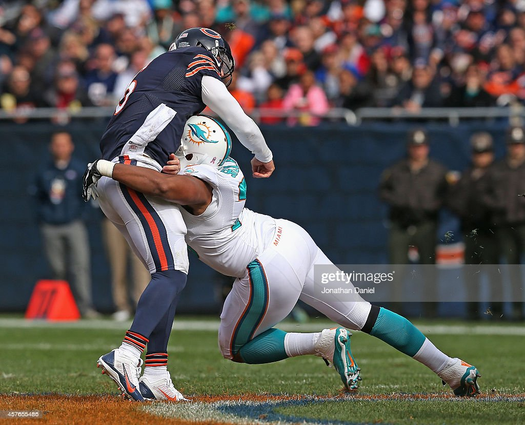 Jay Cutler #6 of the Chicago Bears is hit after passing by Derrick Shelby #79 of the Miami Dolphins at Soldier Field on October 19, 2014 in Chicago, Illinois. The Dolphins defeated the Bears 27-14.