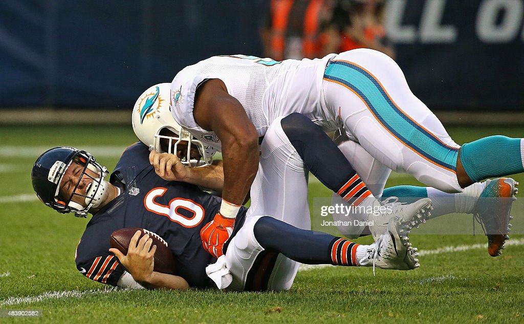 Jay Cutler #6 of the Chicago Bears is hit by Cameron Wake #91 of the Miami Dolphins during a preseason game at Soldier Field on August 13, 2015 in Chicago, Illinois.