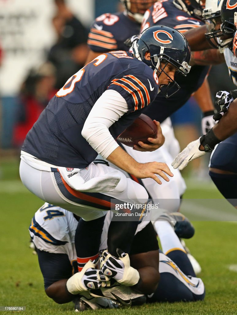 Jay Cutler of the Chicago Bears is sacked by Corey Liuget of the San Diego Chargers at Soldier Field on August 15 2013 in Chicago Illinois