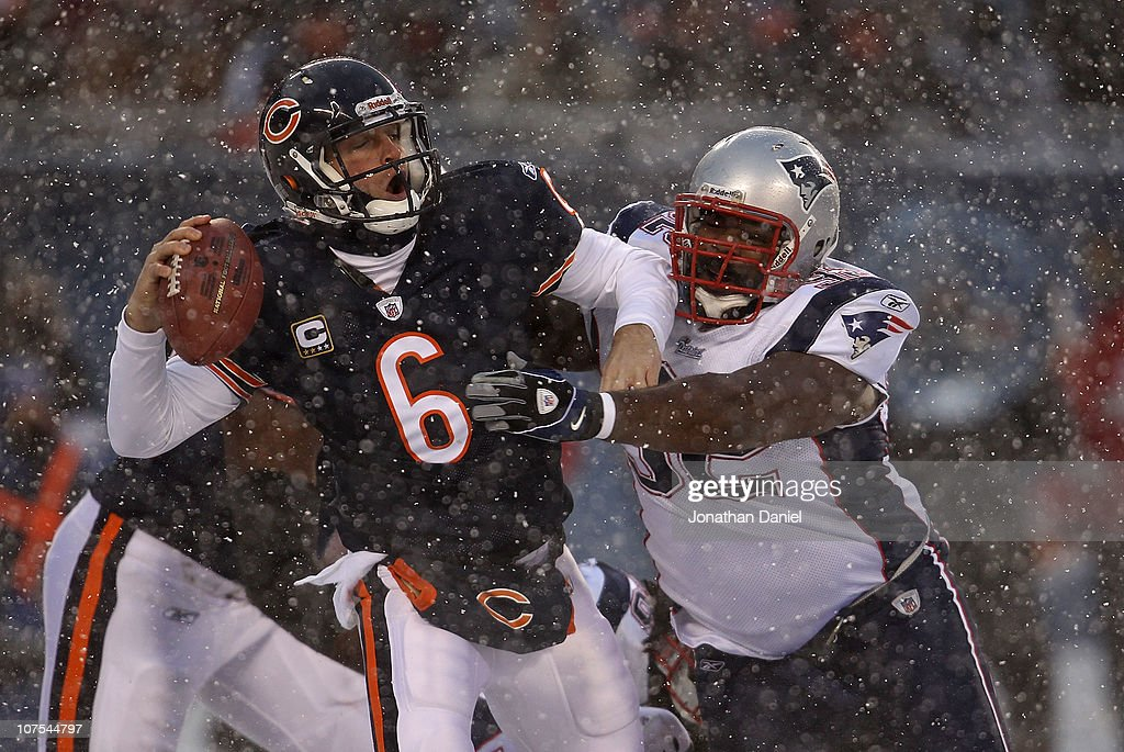 Jay Cutler of the Chicago Bears is sacked by Gerard Warren of the New England Patriots at Soldier Field on December 12 2010 in Chicago Illinois