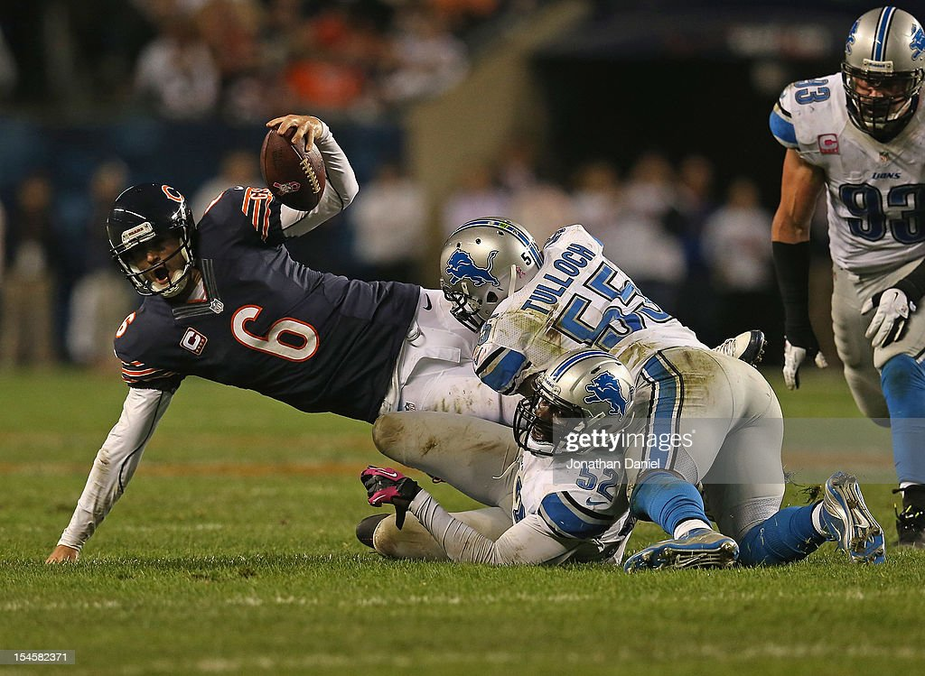 Jay Cutler of the Chicago Bears is sacked by Justin Durant and Stephen Tulloch of the Detroit Lions at Soldier Field on October 22 2012 in Chicago...