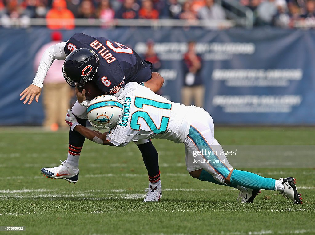 Jay Cutler #6 of the Chicago Bears is tackled by Brent Grimes #21 of the Miami Dolphins at Soldier Field on October 19, 2014 in Chicago, Illinois. The Dolphins defeated the Bears 27-14.